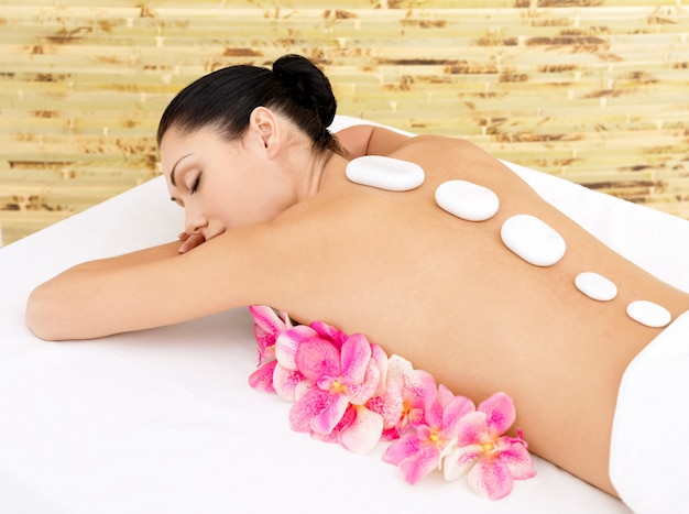 Body care for young woman at beauty spa salon white ot stones on female back