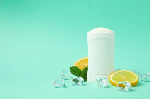 Body deodorant, ice and lemon on mint background, blank space for text