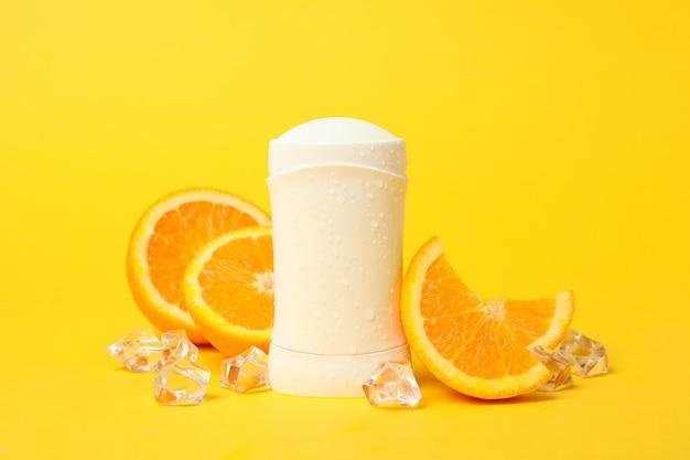 Body deodorant, ice and orange on yellow