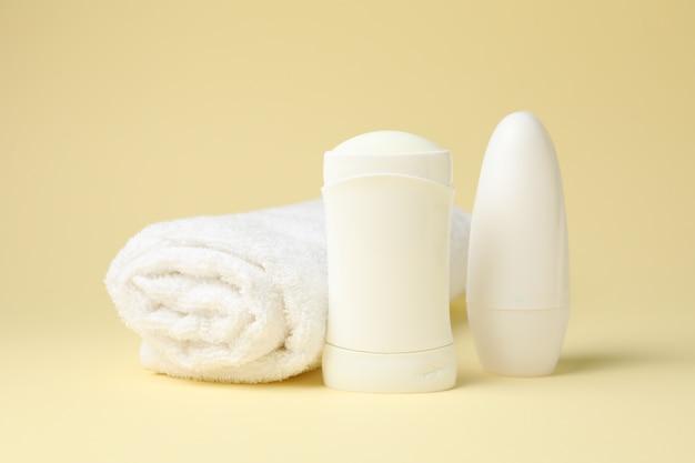Body deodorants and towel on beige