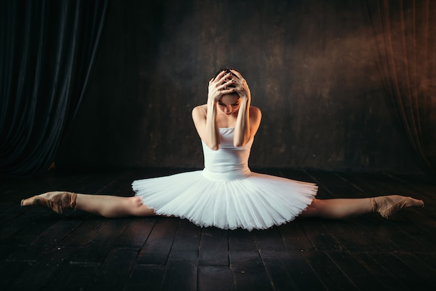 Гибкость тела артиста балета, упражнение на растяжку. балерина в белом платье сидит на шпагате на черном деревянном полу