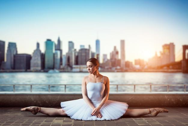 Гибкость тела артиста классического балета. балерина в белом платье сидит на шпагате, вид спереди, городской пейзаж с небоскребами