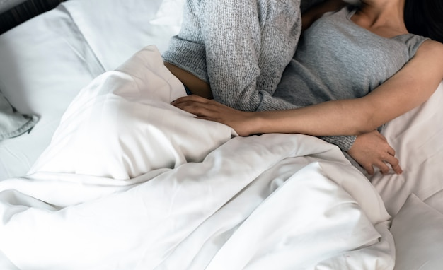 Body and hands of woman love couple laying down on bed,feeling loved,doing love activity together