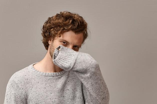ボディーランゲージと人間の表情。灰色の暖かいプルオーバーを着て、鼻と口を手で覆っているトレンディな見た目の狡猾な若いひげを生やした男、彼の表情は謎に満ちています