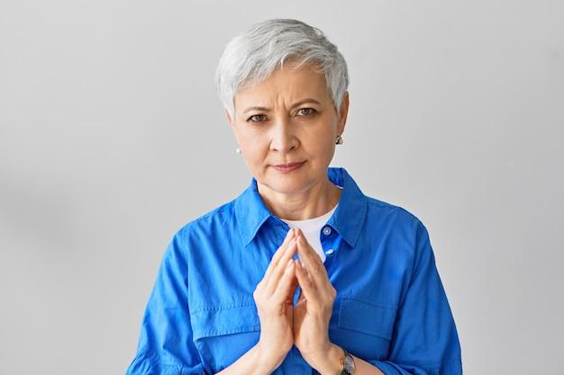 Язык тела. привлекательная седая кавказская дама в стильной синей рубашке с лукавым взглядом сжимает руки, как будто что-то замышляет. серьезная зрелая женщина позирует со сложенными руками
