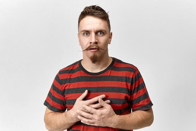 ボディランゲージ。流行に敏感な口ひげとあごひげを生やした魅力的なハンサムなヨーロッパ人の男が口を開け、胸に手をつないで、彼の目は驚きと驚きに満ちています。