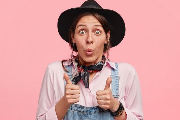 Concetto di linguaggio ed emozioni del corpo. la femmina stupita e piacevolmente sorpresa tiene i pollici alzati, le labbra rotonde con stupore, indossa un cappello nero alla moda, indossa una camicia, isolato sul muro rosa