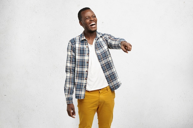 Body language, gestures. portrait of charismatic dark-skinned student wearing checkered shirt, laughing at someone or something, pointing finger at subject, looking happy, cheerful and carefree