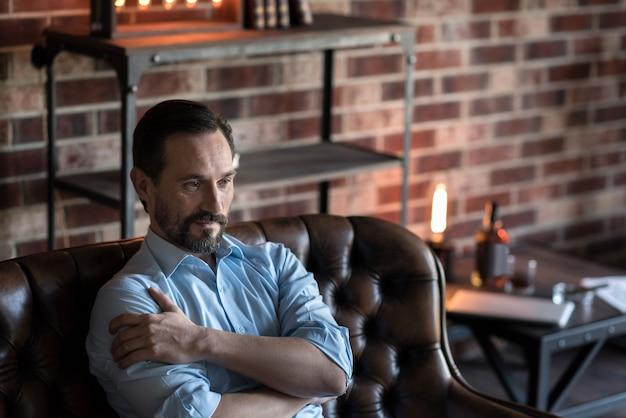 ボディランゲージ。ソファに座って何かを考えながら腕を包む格好良い素敵な気持ちの良い男