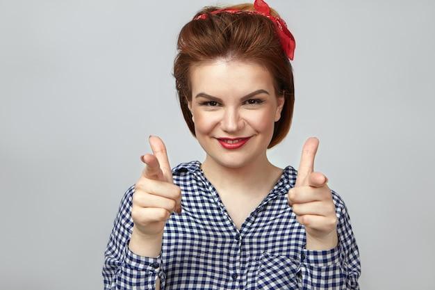 Linguaggio del corpo. splendida giovane pin up donna che indossa il trucco glamour e camicia a scacchi che punta il dito indice