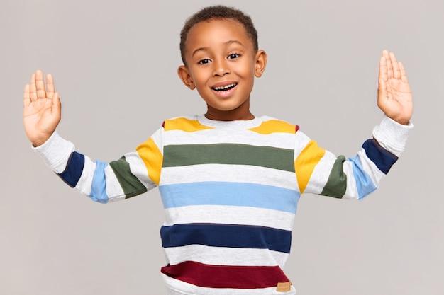 신체 언어. 줄무늬 풀오버에 잘 생긴 사랑스러운 아프리카 계 미국인 소년이 매우 큰 것을 잡고 측정하는 것처럼 손을 넓게 벌리고 흥분된 표정을지었습니다.