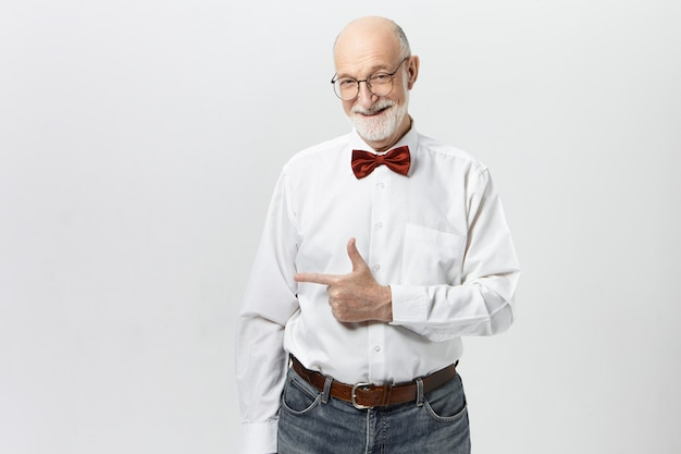 Body language. happy positive elderly man in casual jeans, glasses, shirt and red bow tie smiling, pointing index finger away, indicating blank copyspace wall for your advertising content