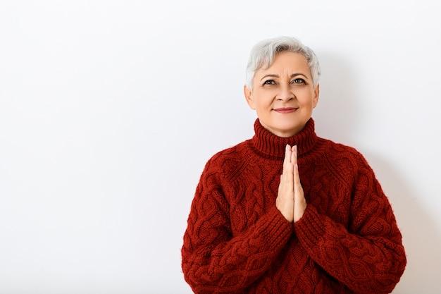 ボディランゲージ。魅力的な美しい白髪の女性の引退時の水平方向のショットは、居心地の良いニットセーターで壁にポーズをとって手を握りしめ、広く笑って、良いニュースに興奮しています