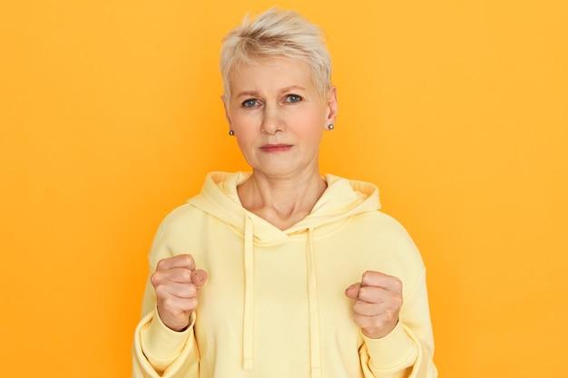 ボディランゲージ。金髪の短い髪型の握りこぶしで欲求不満の動揺した引退した女性の孤立した画像、戦う準備ができて、彼女の強さを示し、パーカーを着て黄色のスタジオの壁でポーズをとる