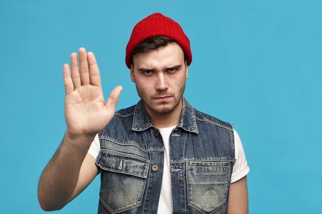 Linguaggio del corpo. colpo isolato del giovane alla moda alla moda in cappello rosso che mostra la reazione negativa