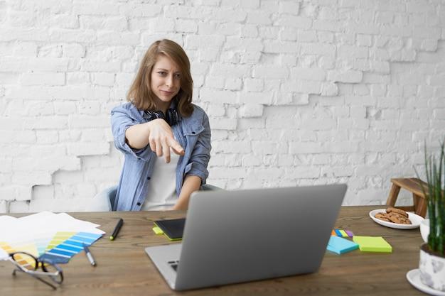 Linguaggio del corpo e concetto di tecnologia moderna. emotiva giovane donna con le cuffie al collo, seduta davanti al computer portatile aperto, sorridente e puntando il dito davanti allo schermo, vedendo qualcosa di divertente