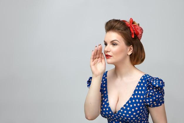 ボディランゲージ。スタジオでポーズをとって、誰かを呼んだり、秘密を耳にささやいたりするように、彼女の口に手をつないでいるローネックカットのヴィンテージドレスを着たファッショナブルな若いヨーロッパの女性の写真