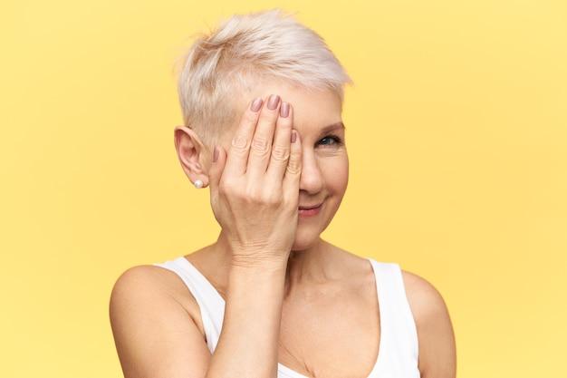 Язык тела. портрет привлекательной женщины средних лет, закрывающей один глаз рукой, проверяя зрение у офтальмолога.