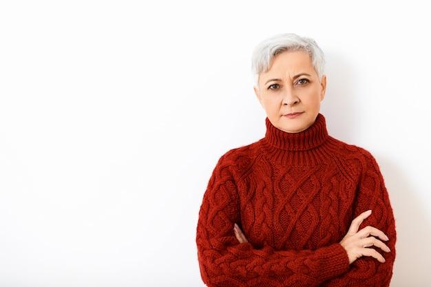 ボディランゲージ。不信感や不本意を表現し、頑固な表情をして、腕を胸に組んで、ニットのジャンパーを着た、引退した魅力的な真面目なヨーロッパの女性の肖像