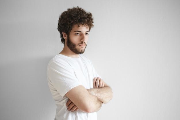 ボディランゲージ。胸にボリュームのある髪型の交差する腕を持つ創造的なひげを生やしたヒップスターの男の肖像画、熟考、アイデア、解決策、または概念を考え、カジュアルな白いtシャツを着て
