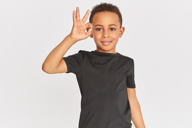 ボディランゲージ。人差し指と親指を接続して承認ジェスチャーをし、大丈夫なサインを示し、すべてが大丈夫だと言って、tシャツを着たフレンドリーな見た目のポジティブな暗い肌の小さな男の子の肖像画