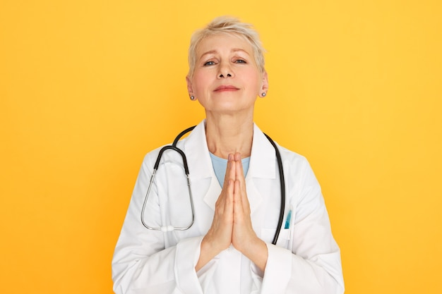 ボディランゲージ。悲しげな表情をして、手を一緒に押して、祈って、末期の患者が回復することを願って、医療ユニの悲しい不幸な中年の女性外科医の肖像画
