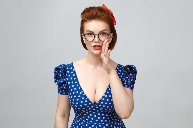 Body language. pretty young european woman wearing glasses, elegant dress and bright make up holding hand at her mouth, sharing top secret or confidential information with you, having mysterious look