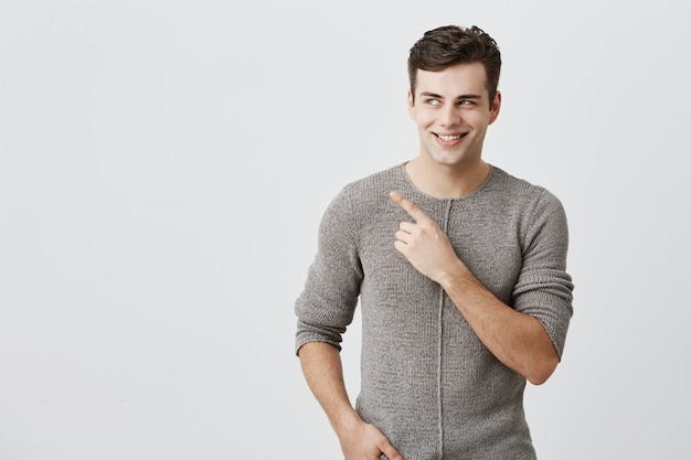 Body language. shocked, excited, surprised guy with dark hair, broadly smiling with teeth, dressed casually, pointing with index finger at copy space for your promotional text or advertisment