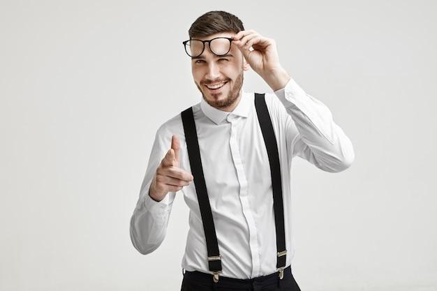 ボディーランゲージ、サイン、ジェスチャー、シンボル。眼鏡を保持し、笑い、カメラに人差し指を向けてスタイリッシュなひげを持つ陽気な成功した若いヨーロッパの男性起業家の肖像画を腰に当てる