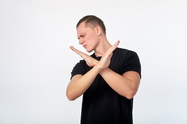 Body language. young unhappy man showing a gesture of denial or stop.