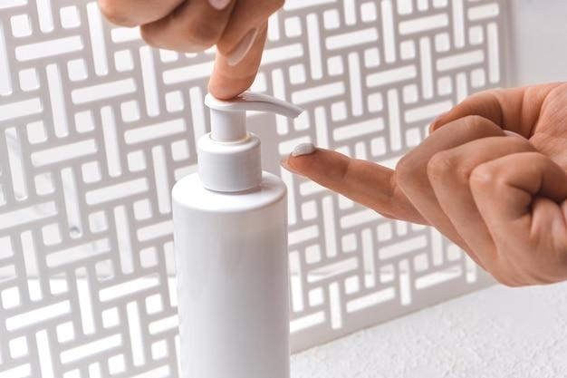 ボディローションスキンケア適用。ボディクリームポンプボトルを保持している女性の手。美容とボディケアのコンセプト。ナチュラルビューティースパ製品コンセプト。モックアップディスペンサー