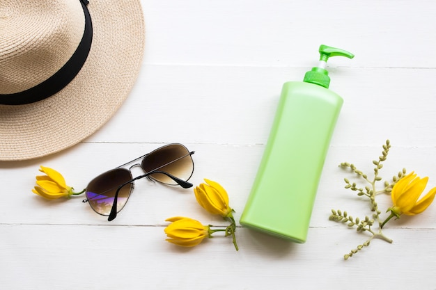 Body lotion and sunglasses on white table