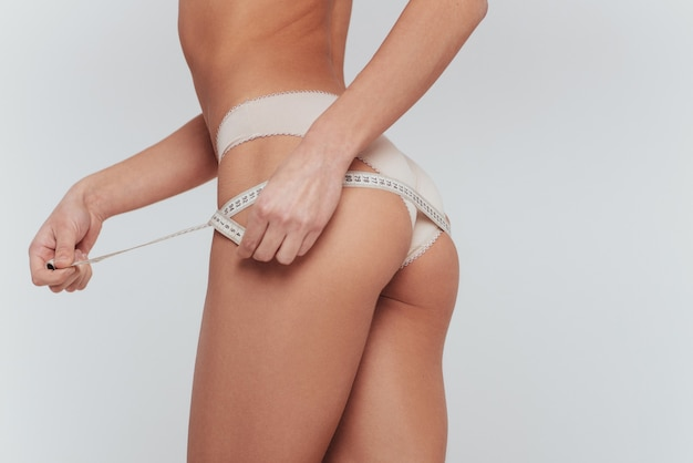 Body measurement in white underwear at the white wall.