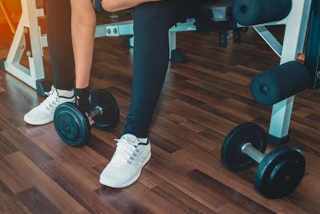 Body and mind workout in loft fitness studio. closeup on woman lifting dumbbell from the floor