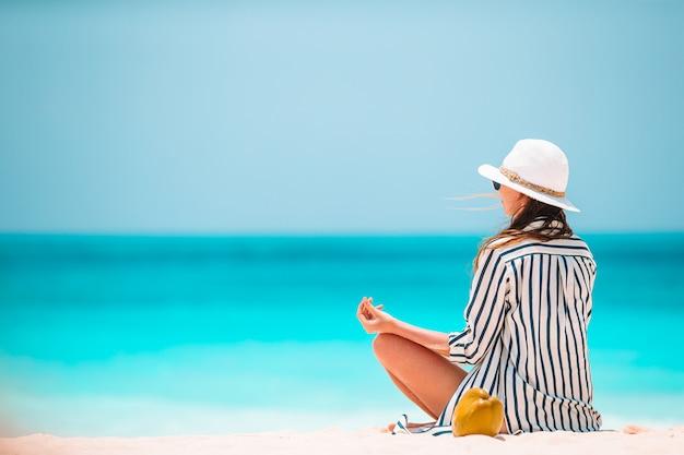 Тело красивой женщины в медитации на пляже