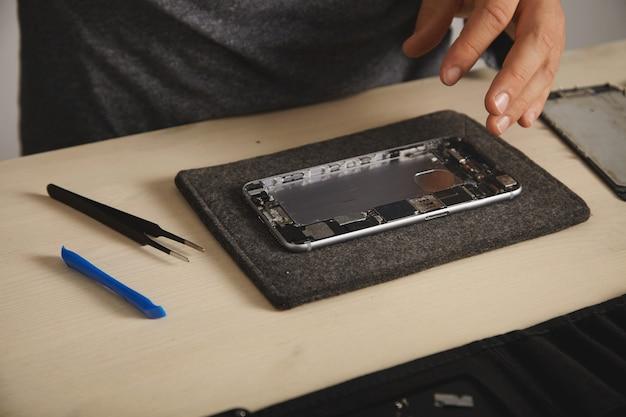分解されたスマートフォンの本体、取り外したリチウムイオン電池で洗浄され、新しい部品を組み立てて取り付ける準備ができています