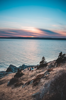 日没時に茶色の岩の形成に近い水の体
