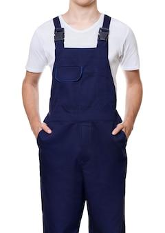 Тело молодого человека, одетого в темно-синий комбинезон и белую футболку с руками в карманах, изолированное на белой стене.