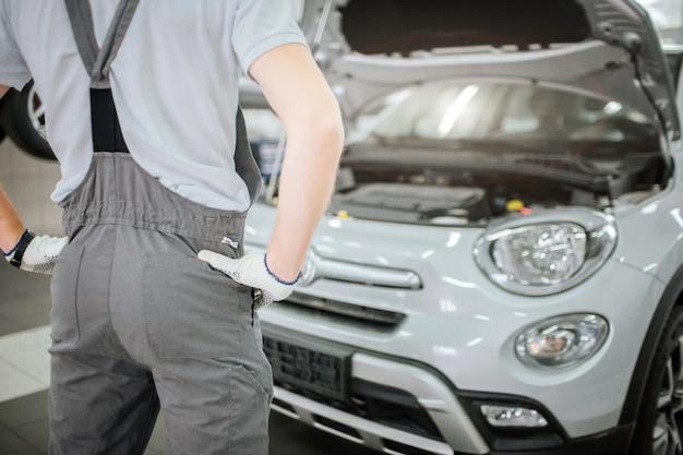 若い男の体は灰色の車の前に立っています。