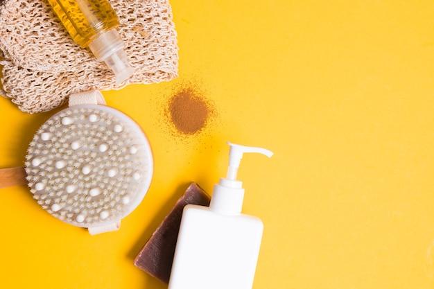 바디 오일, 라벨이없는 디스펜서가있는 흰색 포콘, 마른 마사지 브러시, 수제 초콜릿 비누, 니트 수건 및 노란색 표면에 분쇄 커피