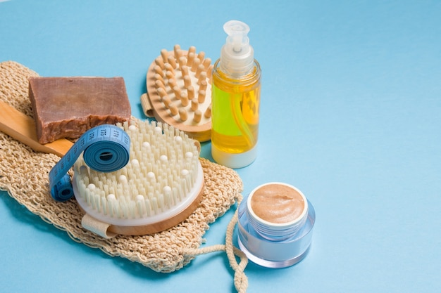Body oil, measuring tape, knitted washcloth, natural homemade scrub in a jar and homemade soap and dry massage brush on a blue surface