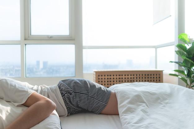 明るい朝、白いベッドで寝る女性の体の部分。