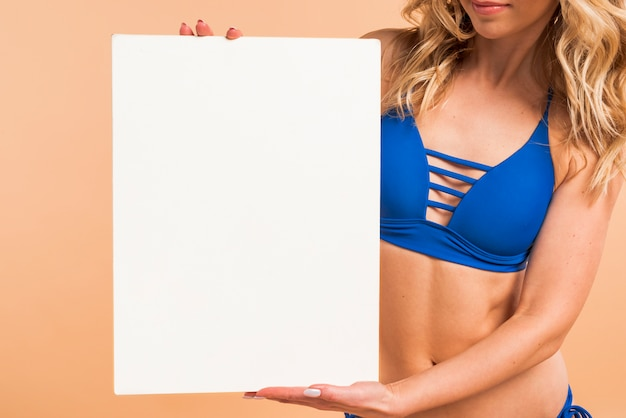 Body part of slim woman in blue bikini with empty board