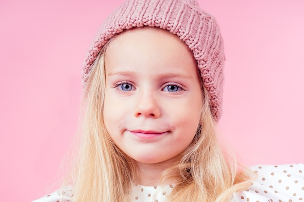 Тело портрет очаровательной маленькой девочки блондинки голубые глаза модель в бежевой вязаной розовой шляпе в белом платье принцессы в горох осенний весенний сезон в студии выстрел на розовом фоне