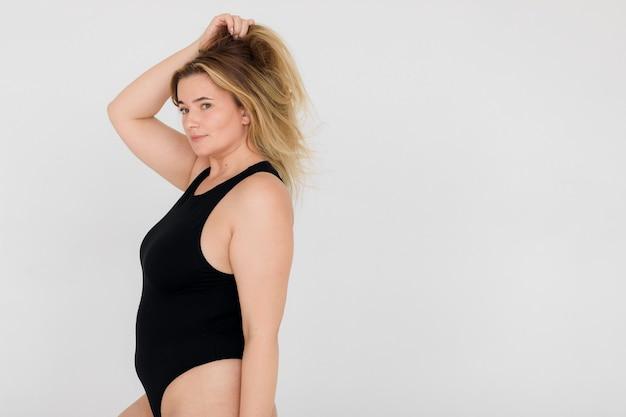 검은 속옷을 입은 긍정적인 여성이 현대적인 흰색 인테리어에 포즈를 취하고 있습니다.