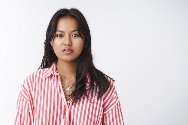 신체 긍정적, 아름다움 및 부드러움 개념. 줄무늬 블라우스를 입은 매력적인 베트남 소녀는 반쯤 벌린 입으로 카메라를 부드럽고 부드럽게 바라보고 흰색 배경에 대해 포즈를 취합니다.