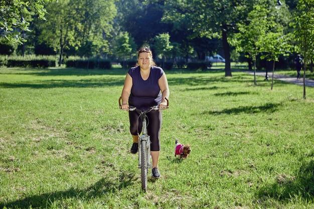 Бодипозитивная женщина катается на велосипеде в городском саду днем
