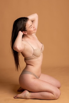 Body positive. a girl in beige underwear poses on a pink background. high quality photo