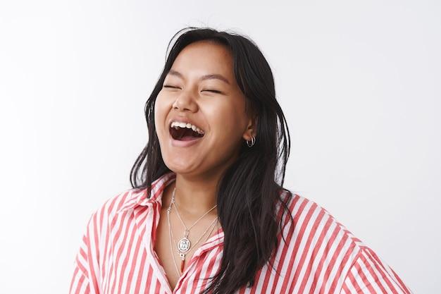 ボディポジティブなライフスタイルと人々のコンセプト。のんきな喜びと前向きな若い幸せな女性幸せと喜びから大声で笑って目を閉じて笑いながら白い背景にニヤリと笑う