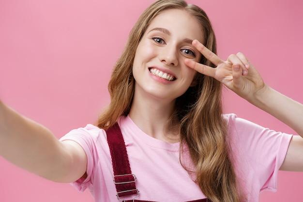 ボディポジティブ、傷跡、スキンポジティブのコンセプト。カメラをつかむために手を引っ張って腕に傷を負った魅力的なのんきな少女の肖像画と広い笑顔で平和のサインを作って自分撮りを取ります。